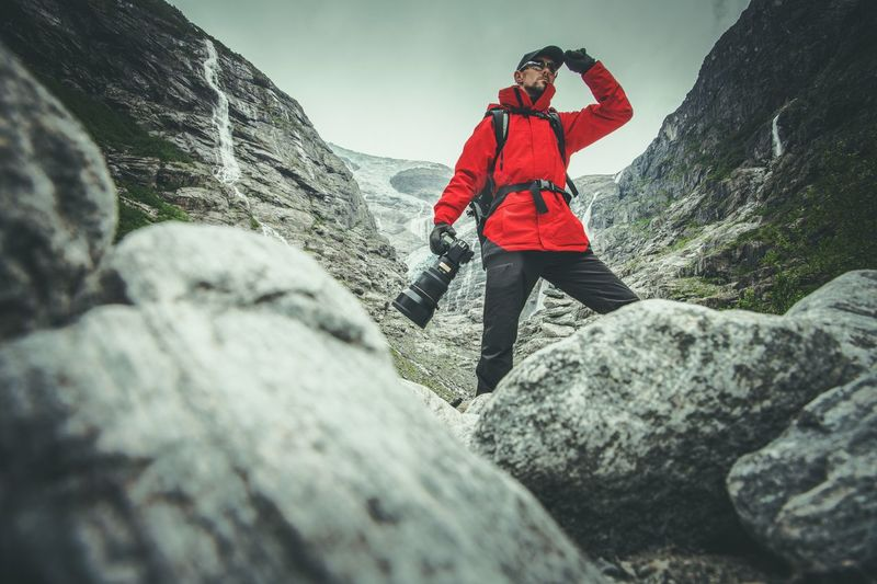 Hiker with digital camera standing on rock against mountain
