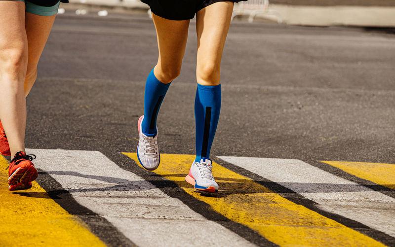 Legs two female runners run in pedestrian crossing