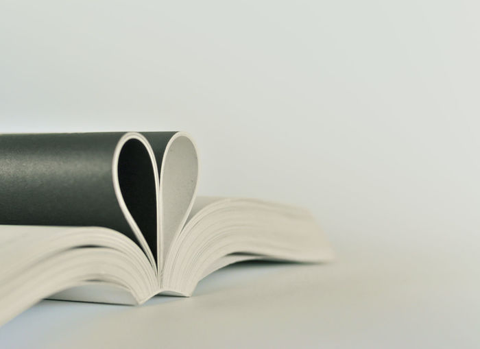Close-up of open book with heart shape on table against white background