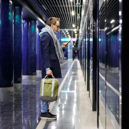 Full length of man using smart phone while standing in illuminated corridor