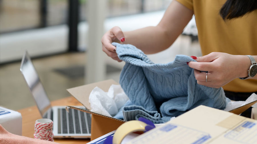 Online selling woman packing sweaters in boxes for delivery to customers, online selling.