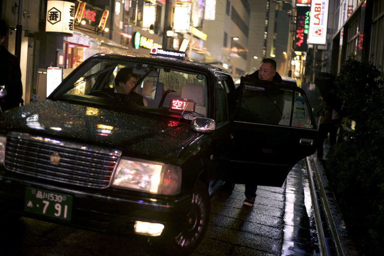 Taxi Architecture Building Exterior Built Structure Car City Group Of People Incidental People Land Vehicle Men Mode Of Transportation Motor Vehicle Night Outdoors People Real People Street Transportation Travel Wet Women