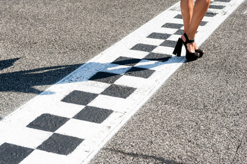 Low Section Of Woman Standing On Finish Line At Motor Racing Track