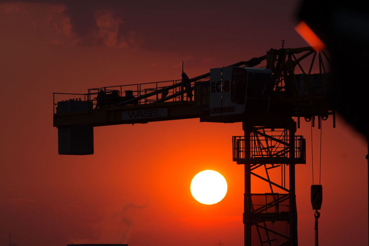 Low Angle View Of Silhouette Crane Against Orange Sky