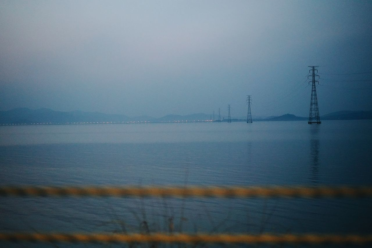 water, sky, no people, fog, nature, sea, built structure, architecture, beauty in nature, scenics - nature, electricity pylon, tranquility, tranquil scene, outdoors, dusk, connection, waterfront, electricity, power supply, bay