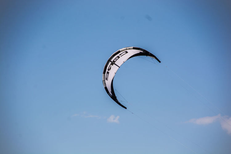 Low angle view of person paragliding against blue sky