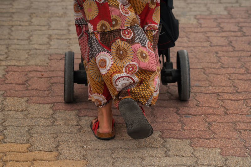 Low Section Of Woman With Baby Carriage Walking On Pathway