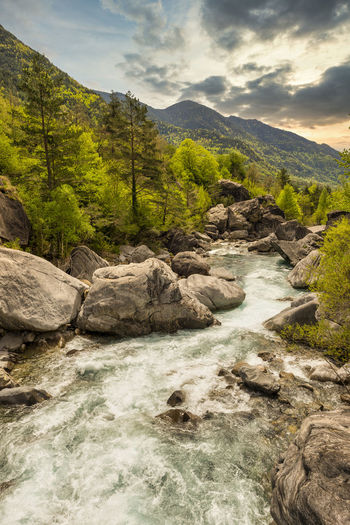 Stream flowing through rocks in mountains against sky