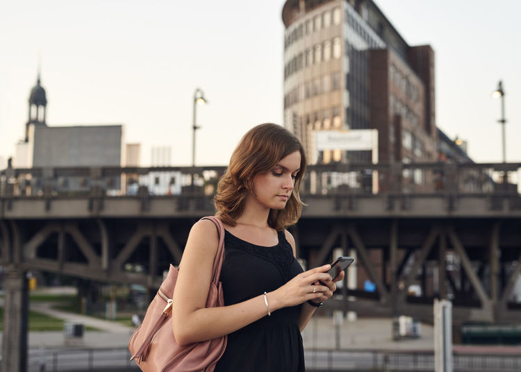 Young woman using smart phone while standing on bridge