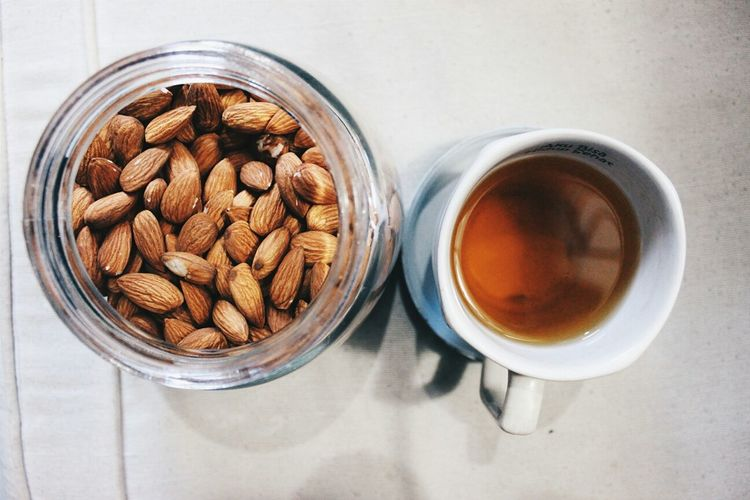 Directly Above Shot Of Almonds In Glass Jar And Tea On Table