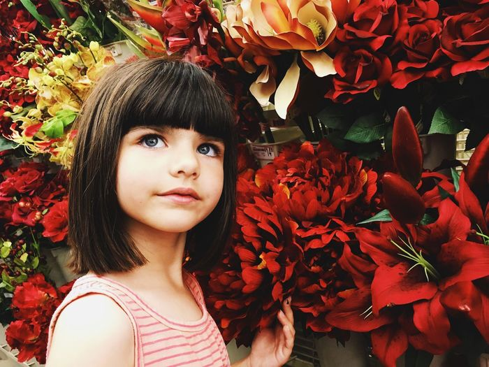 Close-up of girl by artificial flowers in shop