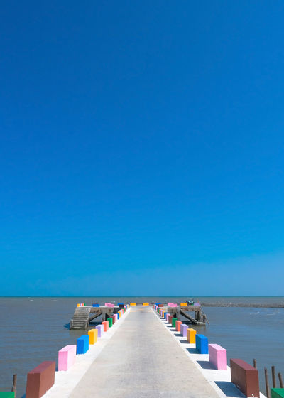 The cement bridge extends into the sea. with colorful barrier panels in the blue sky