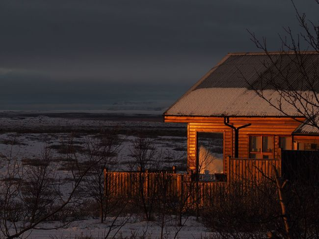 First rays of sun shine on a cabin in the Icelandic wilderness Sky Architecture Built Structure Building Exterior Nature Winter Cold Temperature Cloud - Sky House Land Snow Building Roof Scenics - Nature No People Outdoors Sunrise Morning Light Cabin Wilderness Iceland