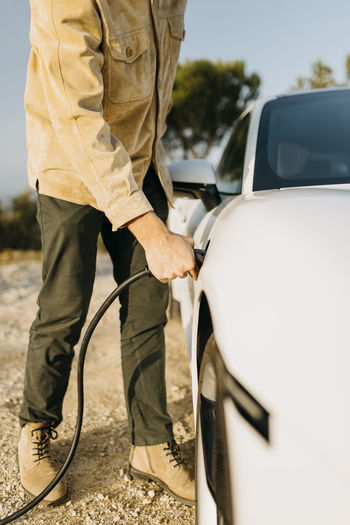Midsection of man holding camera while standing in car