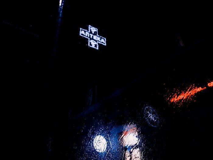 Illuminated text on wet wall at night