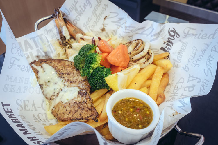 Directly above shot of grilled seafood with vegetables and french fries on paper