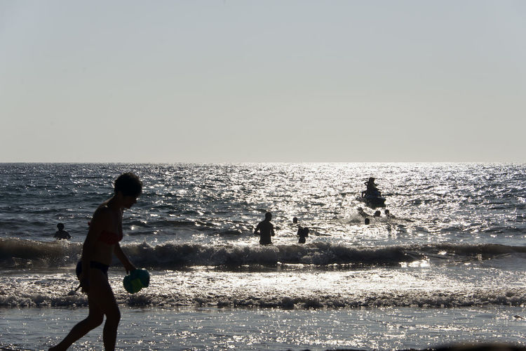 Silhouette of People playing, swimming in the waves in the island of Patmos, Greece in summer time Beach Beauty In Nature Child Childhood Group Of People Horizon Horizon Over Water Land Leisure Activity Lifestyles Men Nature Outdoors People Real People Scenics - Nature Sea Silhouette Sky Water
