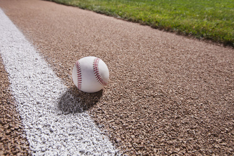 Low angle view of baseball on gravel base path near stripe Baseball Basepath Close-up Day Grass Gravel Ground Low Angle View No People Outdoors Selective Focus Shadow Still Life Surface Level Wide Angle View