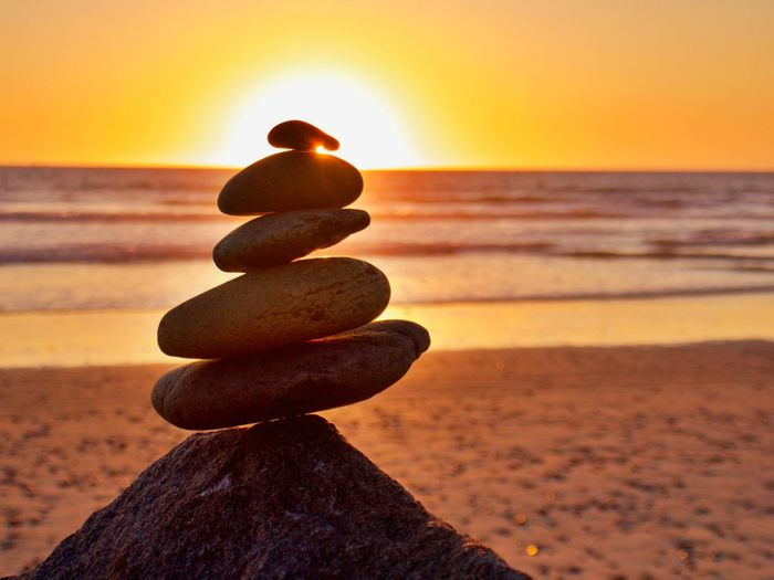 Stack of pebbles on beach during sunset