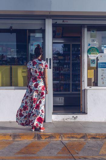 Woman on street against buildings in city