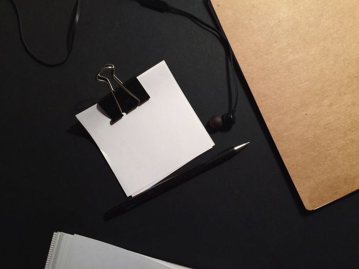 Directly above shot of blank paper with pen and in-ear headphones on table