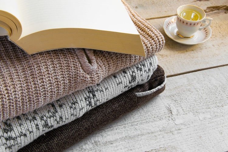High angle view of book on sweater by tea