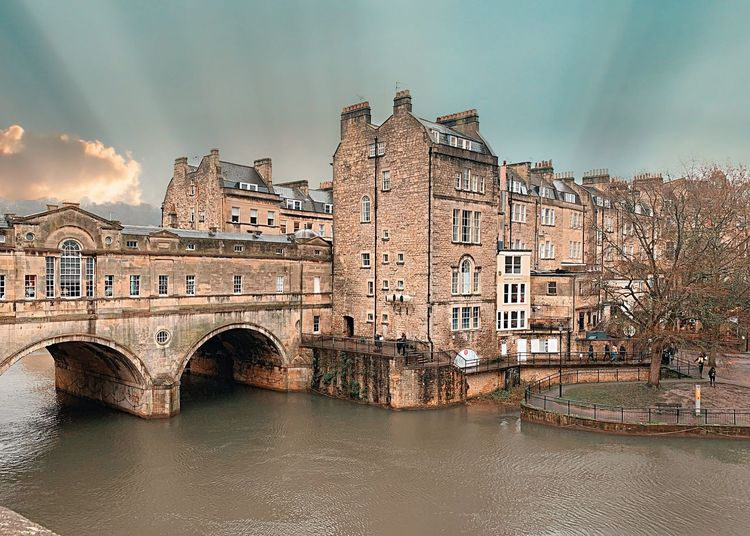 Arch bridge over river against buildings in city