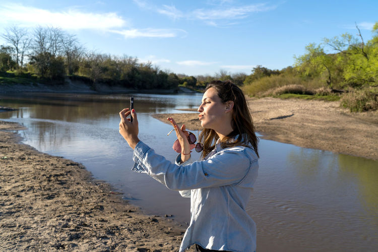 Woman photographing with mobile phone standing in water