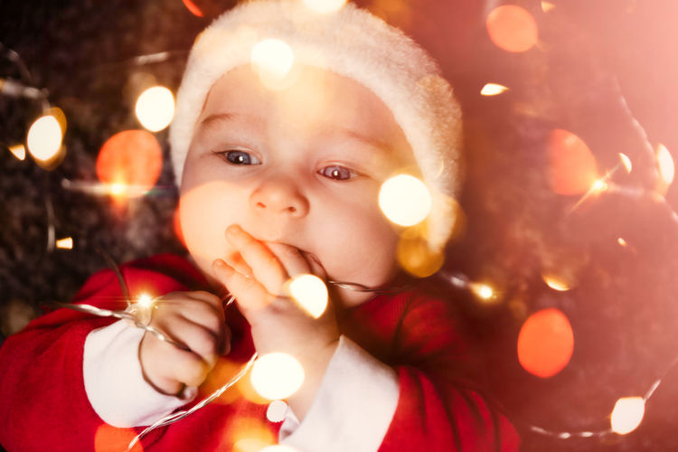 Close-up of cute baby boy in santa costume with illuminated string lights