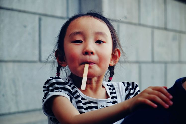 Portrait Of Cute Girl With Ice Cream Stick In Mouth