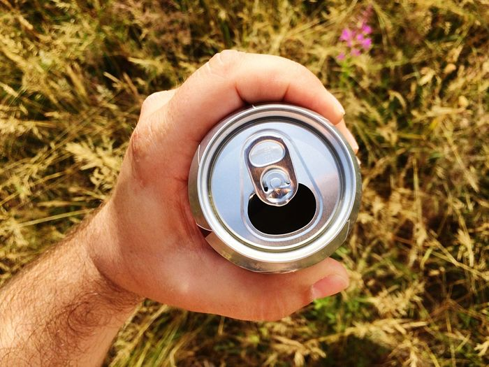 Close-up of man holding beer can