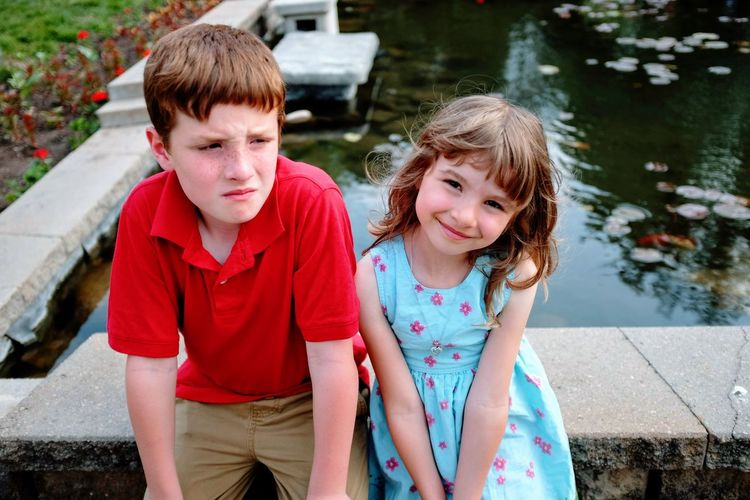 Siblings sitting on retaining wall against pond