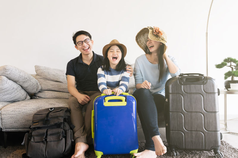 Happy Asian family is preparing for travel at home .Mom daughter and father are packing suitcases for the trip. Asian  Family Happiness Happy Happy People Family Time Home House Daughter Parent Father Mother Dad Mom Love Lifestyles Living Room ASIA Japanese  Korean Thai Taiwan Smiling Smile Fun Portrait Girls Travel Traveling Travelling Map Preparation  Bag Suitcase Clothing Cloth Hat Luggage Luggage Cart  Trip Turism Tourist Tourism