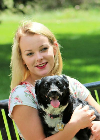 Portrait Of Smiling Young Woman With Dog Sitting At Park