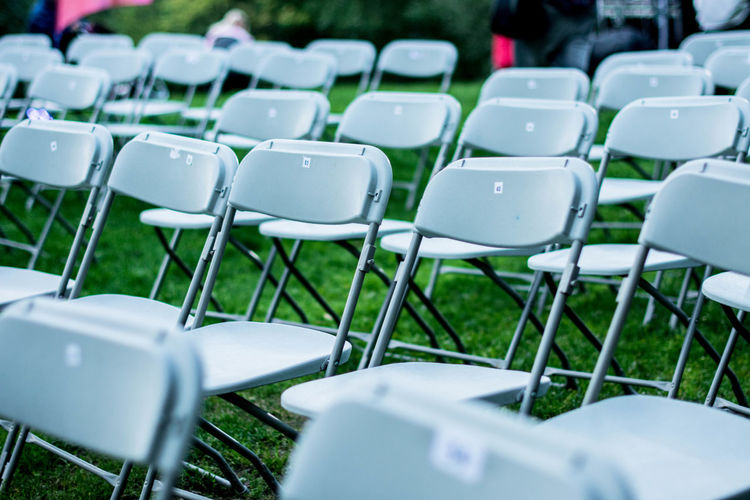 High angle view of chairs arranged on grassy field