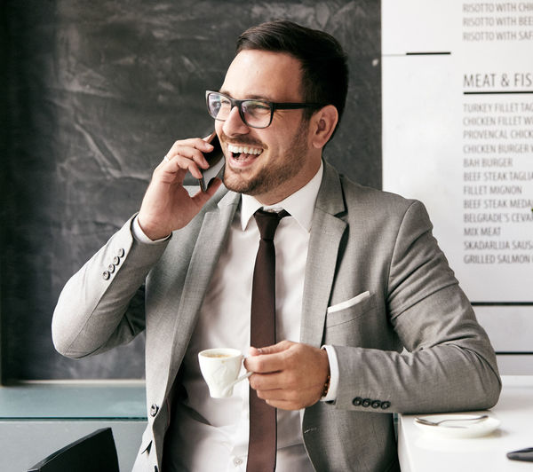 Smiling businessman talking on phone while having coffee