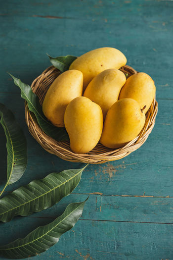 Mango in the basket Food And Drink Food Healthy Eating Freshness Fruit Wellbeing Basket Still Life Table Container Wood - Material No People High Angle View Wicker Bowl Leaf Plant Part Yellow Outdoors Ripe Sour Taste