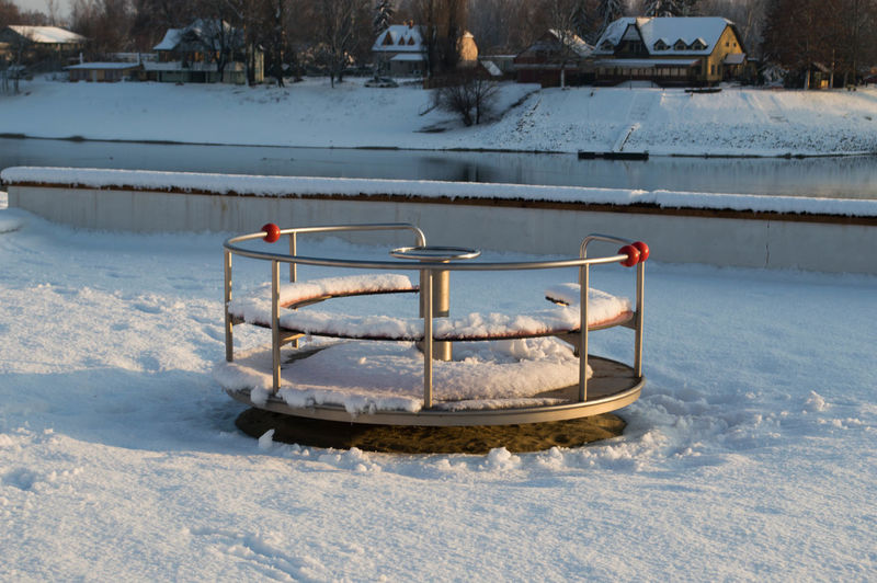 Merry-go-round at snowcapped playground during winter