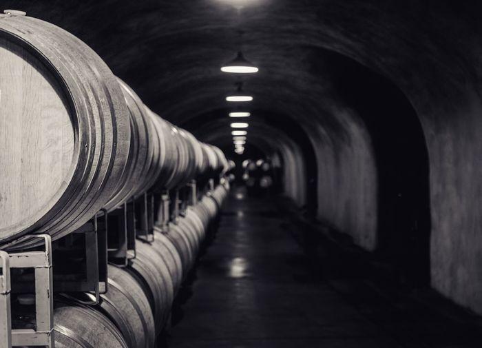 Wine barrels in illuminated tunnel