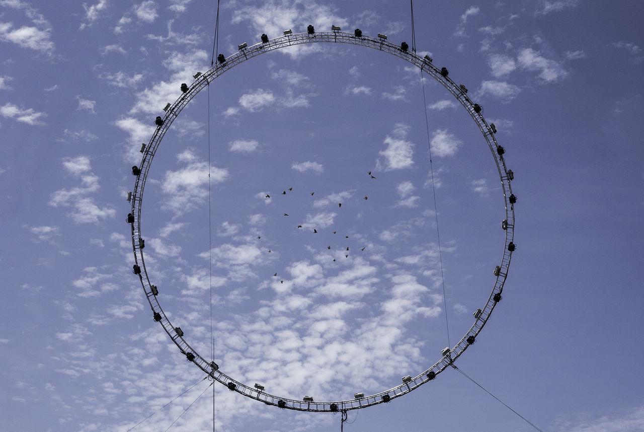 Directly bellow shot of birds flying in sky seen through circular halogen light