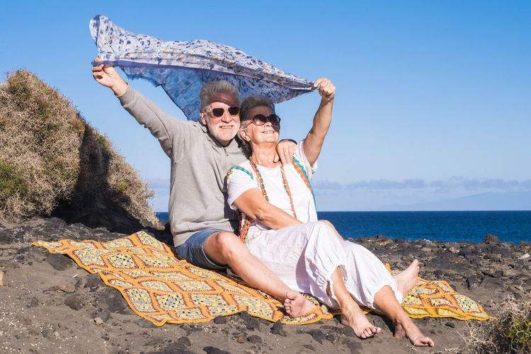 freedom concept for senior adult man and woman playing with the wind in a sunny day in Tenerife Complicity Grandfather Retired Beach Beauty In Nature Couple - Relationship Elderly Front View Full Length Happiness Horizon Over Water Love Men Outdoors Portrait Senior Couple Senior Man Senior Woman Sitting Smiling Summer Togetherness Two People Vacations Wind