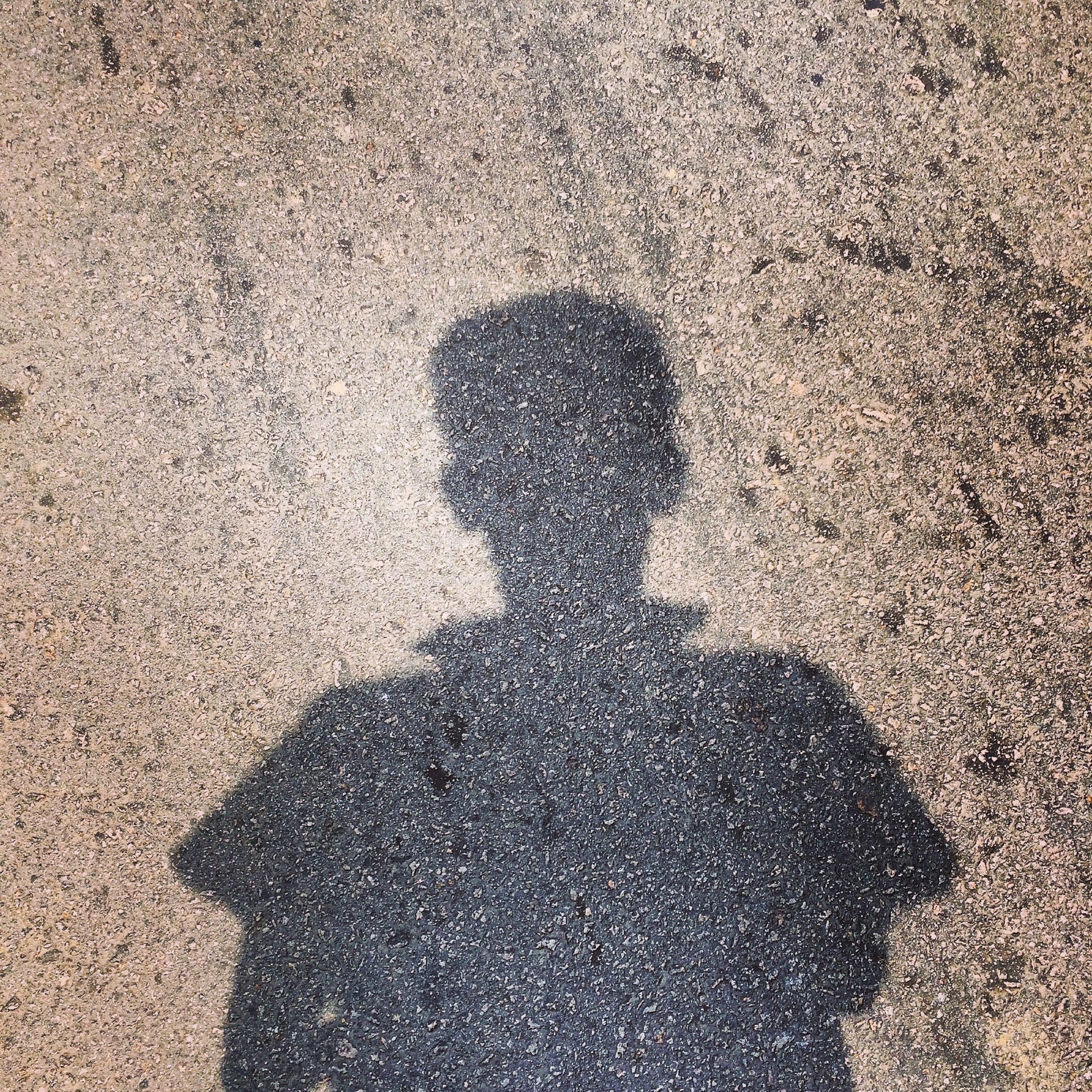 shadow, high angle view, focus on shadow, sunlight, lifestyles, street, leisure activity, silhouette, unrecognizable person, standing, outdoors, day, men, road, sand, outline, walking, ground