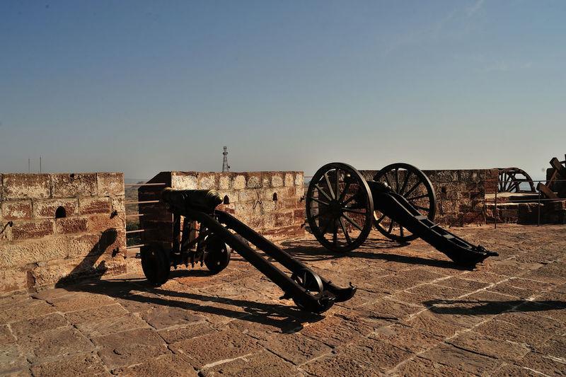 Old metal cart on land against sky