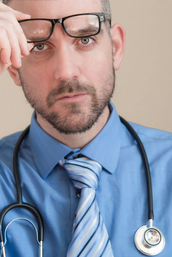 Portrait of doctor holding eyeglasses while wearing stethoscope against wall