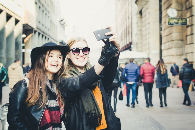 Two women taking selfie with mobile phone in city