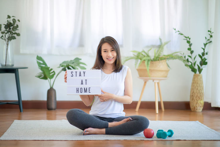 Portrait of a smiling young woman sitting on floor at home
