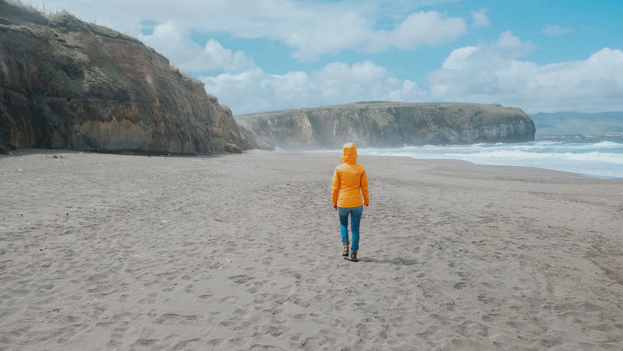 Sao Miguel/ Azores Adult Azores Beach Beauty In Nature Cloud - Sky Day Leisure Activity Nature One Person Outdoor Photography Outdoors Quiet Moments Quiet Places Quiet Thoughts Real People Rear View Rock - Object Sand Sky Standing Tranquility Vacations Walking Woman Yellow Lost In The Landscape