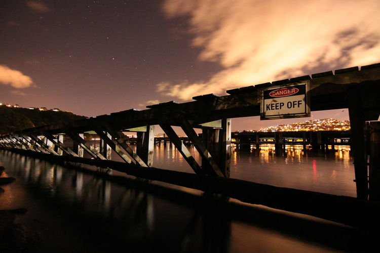Architecture Building Exterior Built Structure Communication Dusk Information Nature Night No People Outdoors Pier Reflection River Sign Sky Text Transportation Water Western Script