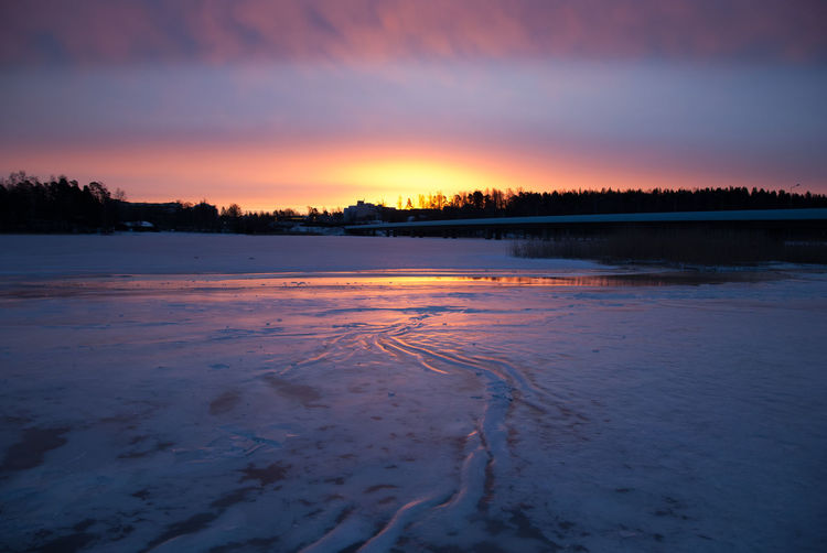 Scenic View Of Frozen Sea Against Orange Sky