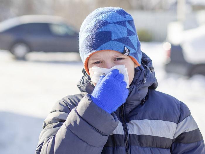 Close-up portrait of boy sneezing
